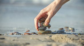 Hand arranging stone stack on a beach. Stock Photography