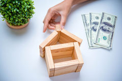 Hand arranging wood block as house. Royalty Free Stock Photography