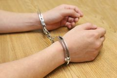 Hand arrested with handcuffs on the wooden table Royalty Free Stock Images