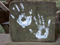 Hand art displayed in park. White paint hand art displayed in park on a wooden log Royalty Free Stock Photography