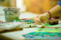 Hand of artist with brush painting picture stock photos