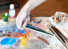 Hand of the artist with a paintbrush Royalty Free Stock Photo