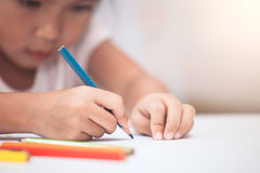 Hand of asian child girl draw and paint with crayon. In vintage color tone Royalty Free Stock Photography