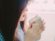 Hand of asian girl in blue flannel shirt hold hot coffee for dri Stock Photography
