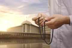 Hand of asian muslim man with prayer beads praying. During sunset Royalty Free Stock Image