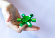 Hand of asian woman spins green fidget spinner Stock Images