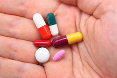 Hand with assorted pills. Hand holding assorted pills and capsules Stock Image
