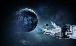 There is life in space. Mixed media. Hand of astronaut and green sprout. Elements of this image are furnished by NASA Royalty Free Stock Photo