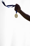 Hand of athlete holding gold medal Stock Photos