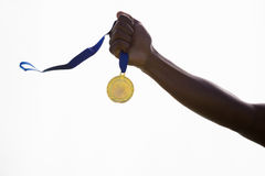 Hand of athlete holding gold medal Royalty Free Stock Photo