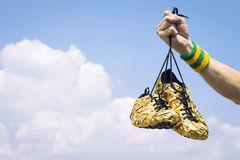 Hand of Athlete Holding Gold Running Shoes Royalty Free Stock Image