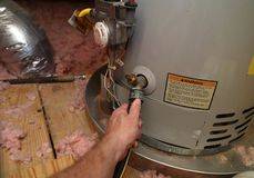 Hand attaches hose to drain water heater. Hand attaches hose to a home water heater to perform maintenance stock photography