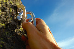 Hand attaching carabiner. To a rock anchors
