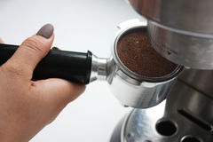 Hand attaching espresso basket to the portafilter Stock Images
