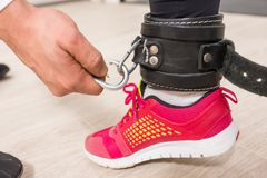 Hand attaching metal clip to leather ankle support stock images