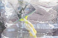 Hand außerhalb des Schabers säubert das Glas Lizenzfreie Stockbilder
