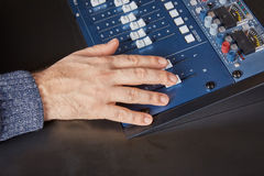 Hand of an audio engineer on a mixing console Stock Photography