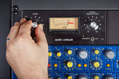 Hand of audio technician turning knob on console Royalty Free Stock Images
