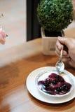 Hand auf Blaubeerkäsekuchen mit Blumenstrauß der künstlichen Blume auf dem Holztisch lizenzfreies stockbild