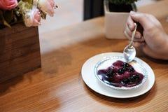 Hand auf Blaubeerkäsekuchen mit Blumenstrauß der künstlichen Blume auf dem Holztisch stockfotos