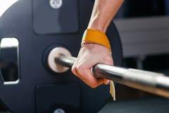 Hand auf dem Barbell Junger Athlet, der zum Gewichthebentraining Carpalverband fertig wird Lizenzfreies Stockbild