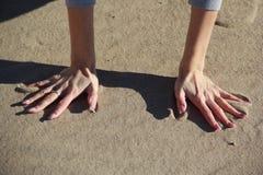 Hand auf dem Sand Stockbild