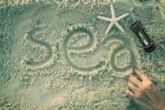 Hand auf dem weißen Sand Stockbild