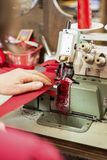 Hand auf der Nähmaschine, die Stoff näht und trimmt Stockfoto