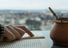 Hand auf einem Buch - Leser trinkendes yerba lizenzfreie stockfotos