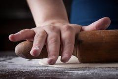 Hand auf einem Nudelholz, das Pizzateig zubereitet Stockfoto