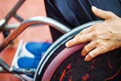 Hand auf einem Rad des Rollstuhls stockfotos