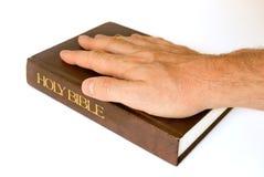 Hand auf einer Bibel Stockfoto