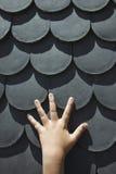 Hand auf geformten Schindeln der Skala. Stockfotos
