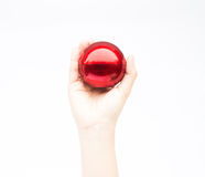 Hand auf glänzendem rotem Ball auf weißem Hintergrund Lizenzfreies Stockfoto