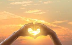 Hand auf Herzsonnenunterganghintergrund Die helle Entstörung durch das Herz zeigt Liebe Stockbild