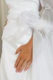 Hand auf Hochzeitskleid stockbild