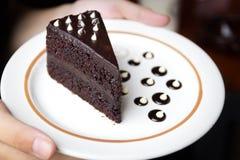 Hand auf Stück des Schokoladenkuchens Lizenzfreies Stockfoto