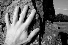 Hand auf stehenden Steinen Stockbild