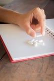 Hand auf weißer Pillenmedizin Stockfotografie