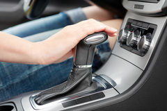 Hand on automatic gear shift. Woman in luxury car stock image