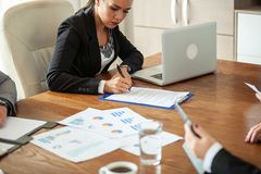 Hand av affärskvinnan som undertecknar ett avtal i meetinfrummet royaltyfri bild