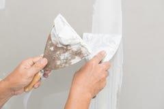Hand av arbetaren med murbruk och mursleven till gipsbrädet Royaltyfria Foton