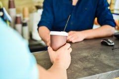 Hand av baristaen på stångservekaffe för klient Handen ger koppen till klientbesökaren Tyck om din drink Mannen mottar drinken på royaltyfri bild