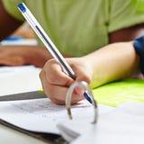 Hand av barnet med pennan i skola Arkivfoton