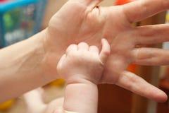 Hand av behandla som ett barn på handen för moder` s Arkivfoton