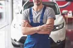 Hand av bilmekanikern med skiftnyckeln Garage för auto reparation royaltyfri fotografi