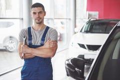 Hand av bilmekanikern med skiftnyckeln Garage för auto reparation arkivbilder