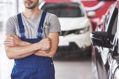 Hand av bilmekanikern med skiftnyckeln Garage för auto reparation royaltyfria bilder