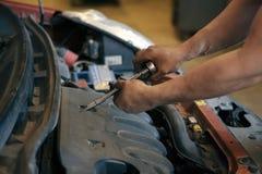 Hand av bilmekanikern med skiftnyckeln Garage för auto reparation royaltyfri foto