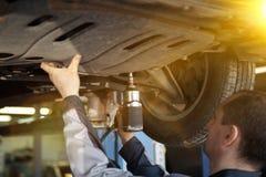 Hand av bilmekanikern med skiftnyckeln Garage för auto reparation fotografering för bildbyråer